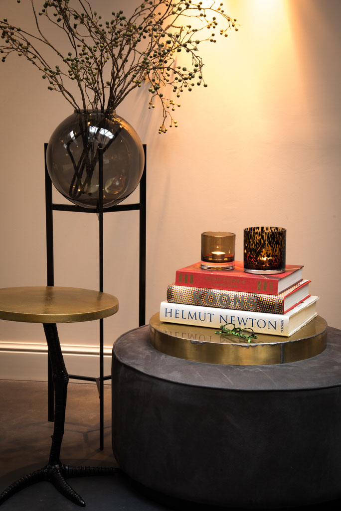 Glass ball vase on a three-legged stand, next to a chicken-legged side table, and a pair of votives atop a stack of books.
