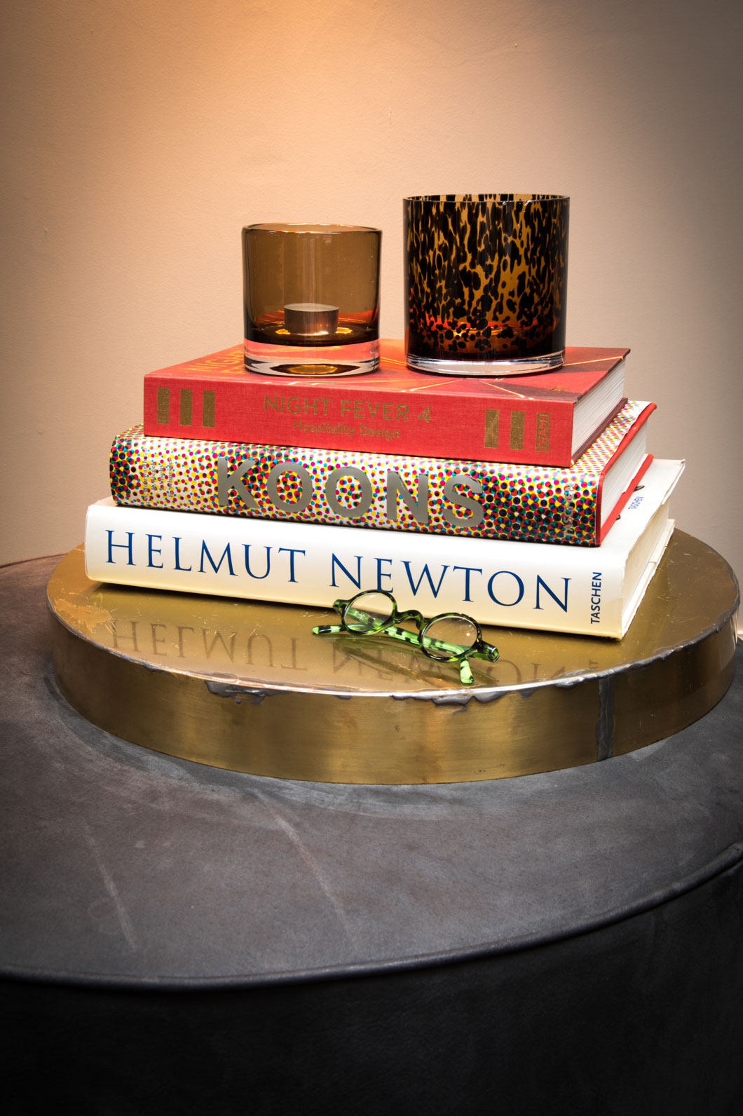 Smoke and leopard-spotted class votives sitting atop a stack of books.