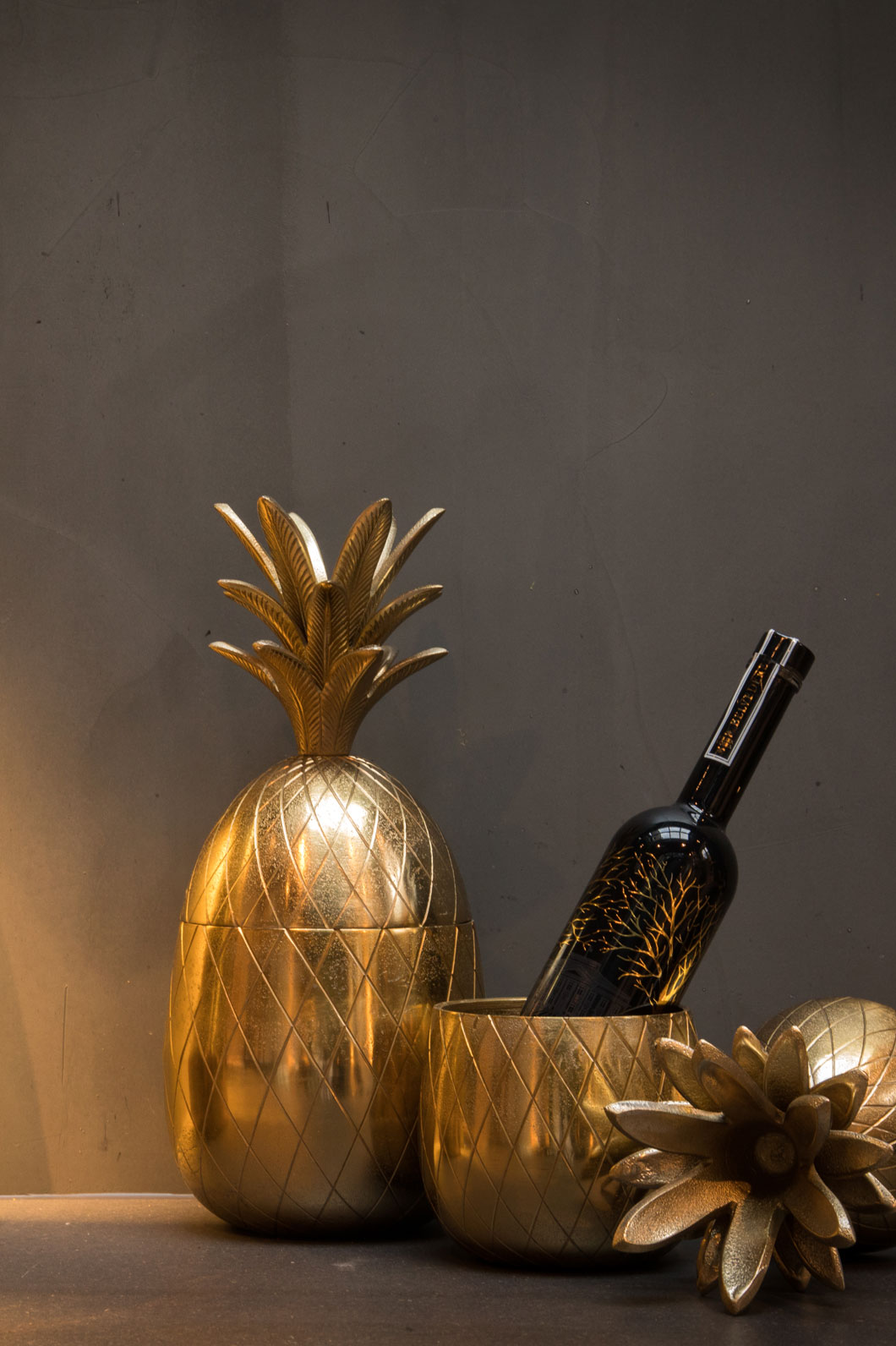 Golden pineapple-shaped drinks holders, one open containing a bottle of wine.